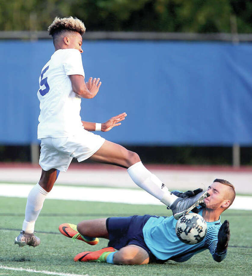 Quincy High's Jaeden Smith, left, narrowly avoids Alton goalkeeper Hunter Dill as Smith tries to get a shot on goal Saturday at Flinn Stadium in Quincy. Photo: Phil Carlson, Quincy Herald-Whig | For The Telegraph