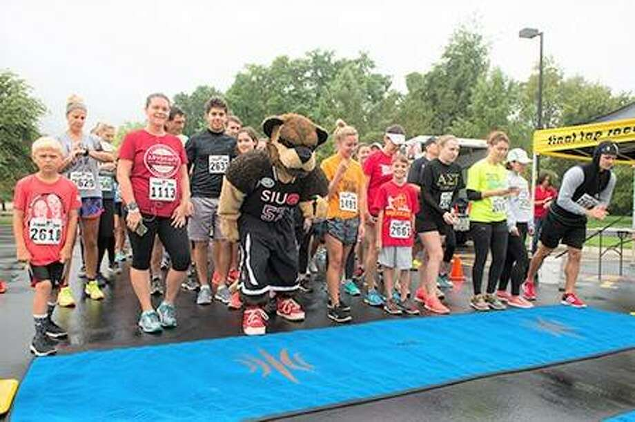 Runners take their places at the starting line alongside SIUE's Eddie the Cougar during the inaugural Cougars Unleashed Homecoming Run. Photo: For The Telegraph