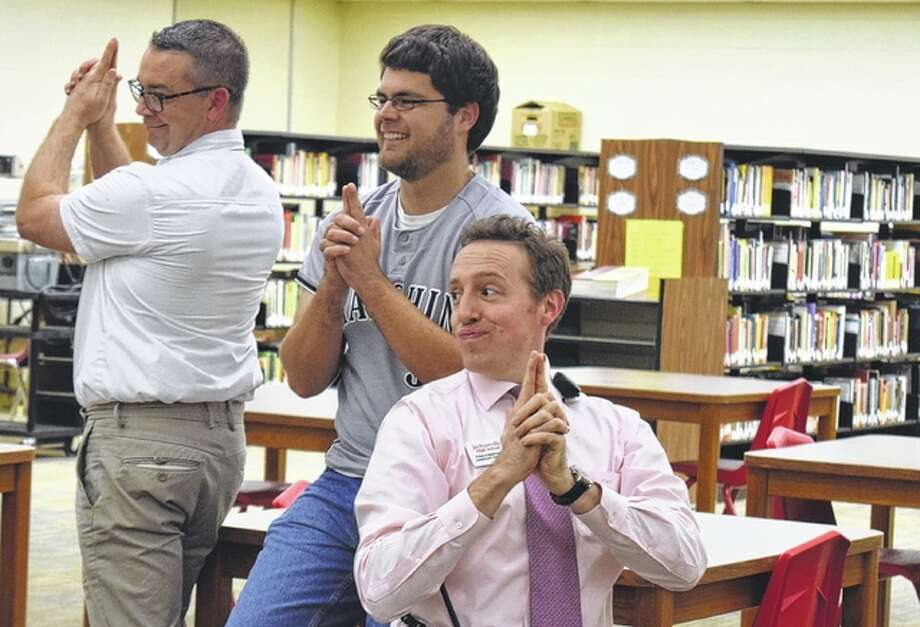 """Scott March (from left), Nate Paulus and Tim Chipman strike a pose from the television show """"Charlie's Angels"""" during the Something on Thursday Afternoons program at Jacksonville High School. Teachers and staff members meet every other week to trade ideas and hear about professional development opportunities. Photo: Samantha McDaniel-Ogletree 