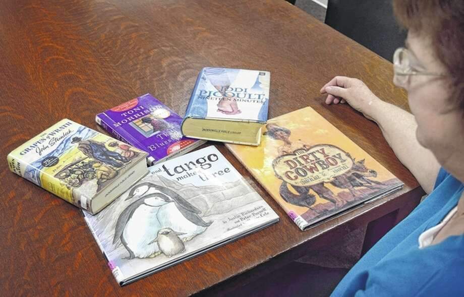 Jacksonville Public Library outreach librarian Diane Hollendonner looks over some of the library's books that have either been banned or challenged in public or school libraries. This is the American Library Association's Banned Books Week. Photo: Greg Olson | Journal-Courier