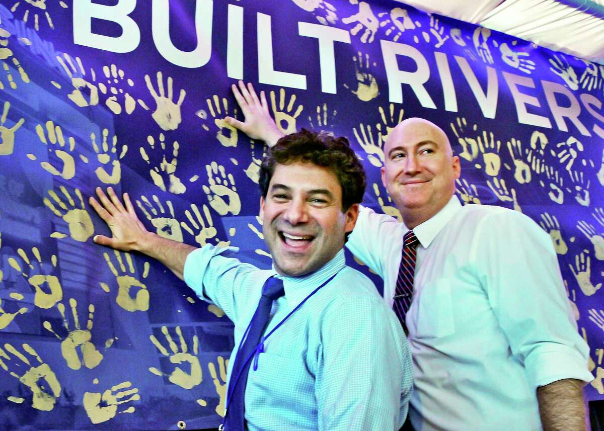 Rush Street Gaming CEO Greg Carlin, left, and Rivers Casino assistant general manager Justin Moore add their hand prints to the