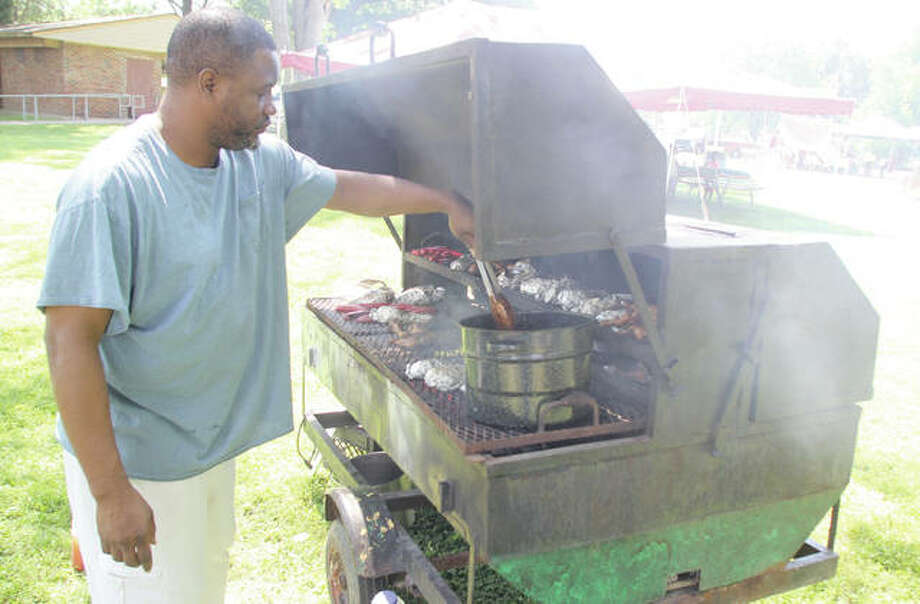 Scott Cousins/The Telegraph Mike Hilliburton stirs pork steaks as they simmer in barbecue sauce at the 25th annual Juneteenth Celebration at the James H. Killion Park in Alton.