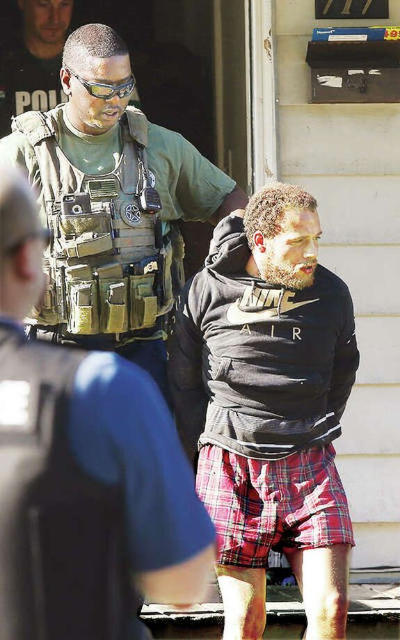 A U.S. Marshal escorts Steven Copenhaver, 26, out of a house in the 700 block of East Sixth Street in Alton Thursday morning following his arrest on what police said was a parole violation. An Alton Police canine unit was called to the scene to search the house, where Copenhaver was apparently found hiding in the attic. Photo: John Badman | The Telegraph
