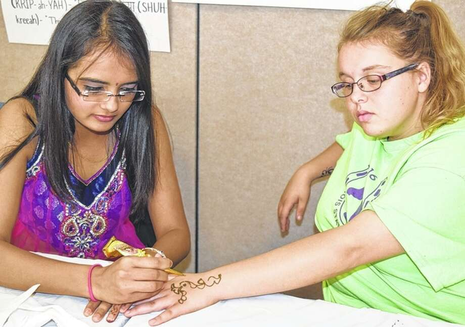 Aditi Shah (left) draws a design on Morgan Lonergan's hand using henna during the Multicultural Fair at Lincoln Land Community College in Jacksonville on Thursday. Photo: Samantha McDaniel-Ogletree | Journal-Courier