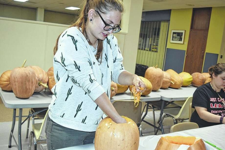 MacMurray College senior Allison Becker cleans out a pumpkin before carving it Friday night in the Gamble Campus Center. Photo: Samantha McDaniel-Ogletree | Journal-Courier