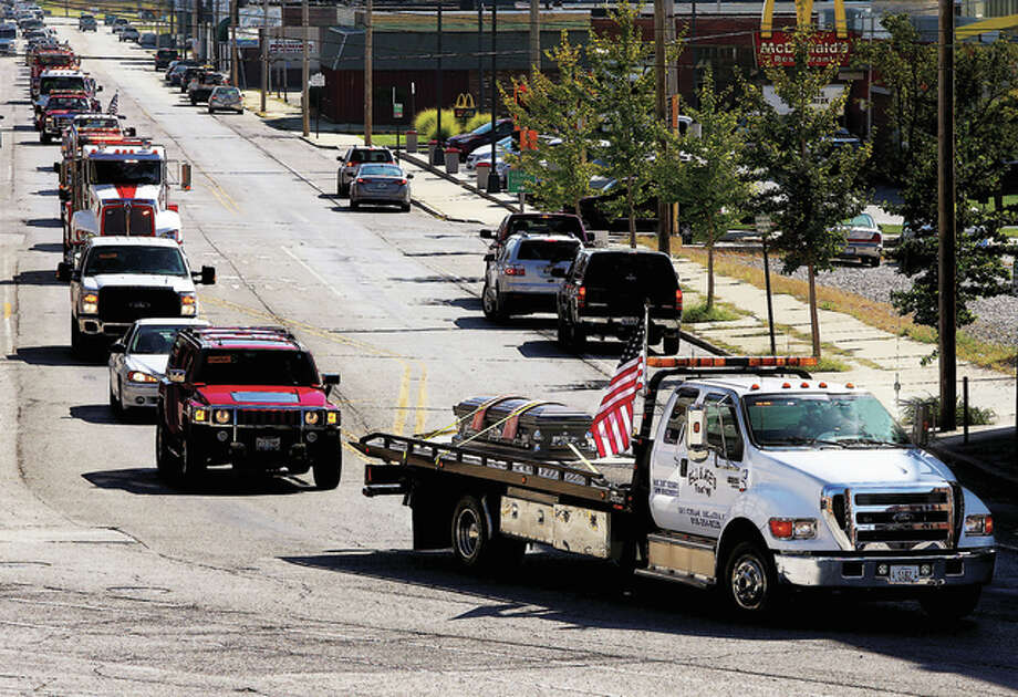 "The casket of Richard ""Dick"" Klaffer, owner of Bill and Joe's Towing, rides on a flatbed truck followed by tow truck operators during a funeral procession in Alton. Klaffer, 63, died Sept. 30."