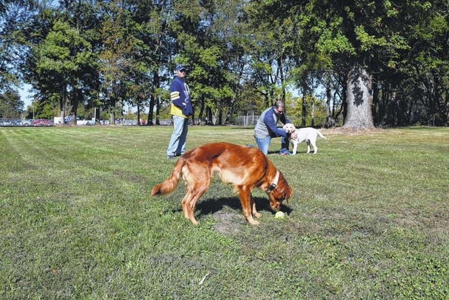 Brett Castleberry of Jacksonville (left) and his golden retriever, Ginger (foreground), walk around the new Jacksonville PetSafe Dog Park Saturday with Travis Richardson of Jacksonville and his yellow Labrador retriever, Cash. The seven-acre dog park on East Vandalia Road officially opened Saturday. Photo: Greg Olson | Journal-Courier