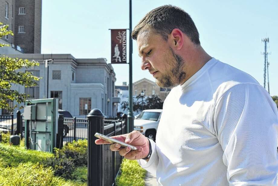 Braden Guinn of Concord, a student at Lincoln Land Community College, checks his phone Tuesday in Jacksonville's Central Park. Smartphone, tablet and laptop users will now be able to connect to a free wireless network put into place downtown. Photo: Nick Draper | Journal-Courier