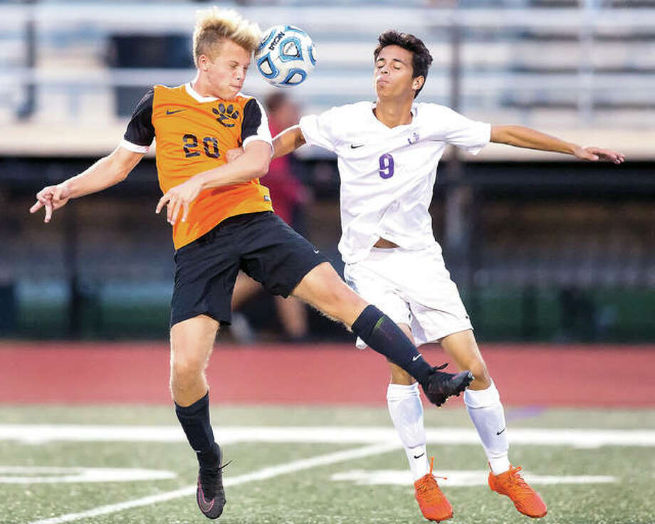 Edwardsville's Nick Doll (20) and Julian Cardenas of Collinsville battle for the ball during SWC soccer action Tuesday night in Collinsville. Photo: Scott Kane | For The Telegraph