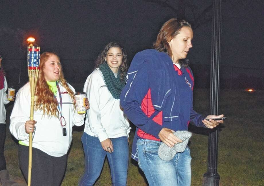 MacMurray College students walk down Clay Avenue Friday night during a torchlight parade. The students walked around the campus before attending their homecoming pep rally. Photo: Samantha McDaniel-Ogletree | Journal-Courier