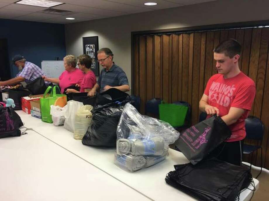 Volunteers stuff care packages to be given to cancer patients at Anderson Hospital. Photo: For The Telegraph