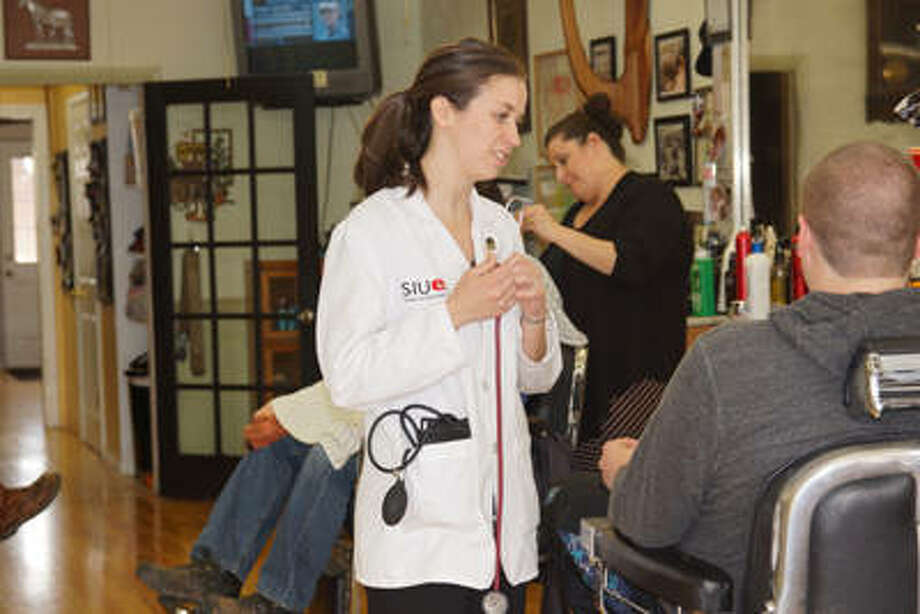 SIUE School of Pharmacy alumnus Emily Mahill performed blood pressure screenings at Eaker's Barber Shop while participating in a previous Blood Pressure Blitz. Photo: For The Telegraph