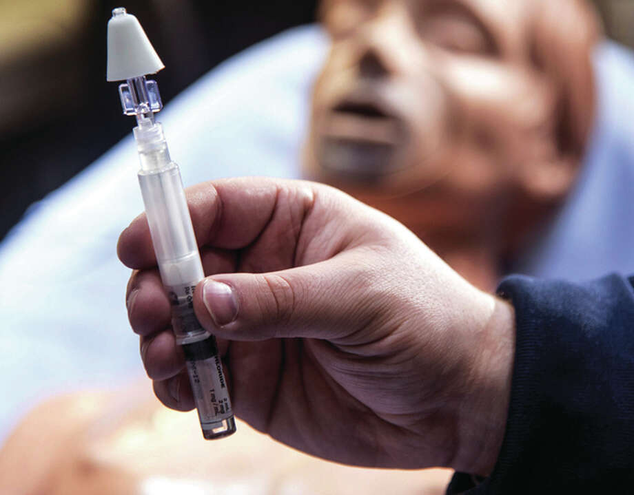 John Dixon | The News-Gazette (AP) Chris Humor, a paramedic for Carle Arrow Ambulance in Champaign, holds a syringe with a mist atomizer used to dispense Narcan, an emergency life-saving opiate antidote for heroin overdose victims.