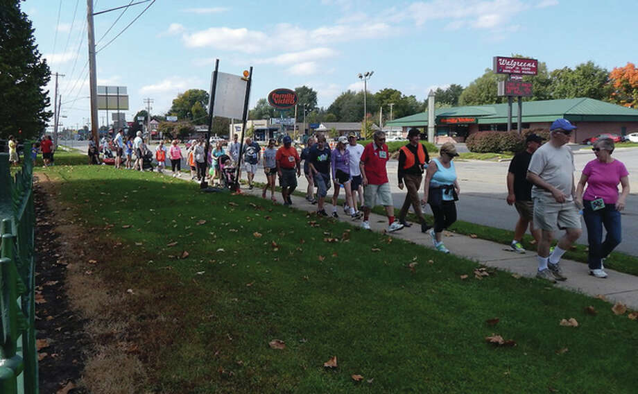 Walkers participating Sunday afternoon in the Morgan County CROP Walk begin their journey along Morton Avenue at Community Park. The annual walk, sponsored by Church World Service, raises funds to help end hunger on both a community level and an international level. A portion of the funds raised Sunday by around 60 walkers will benefit food programs in Morgan County. Photo: Angela Bauer | Journal-Courier