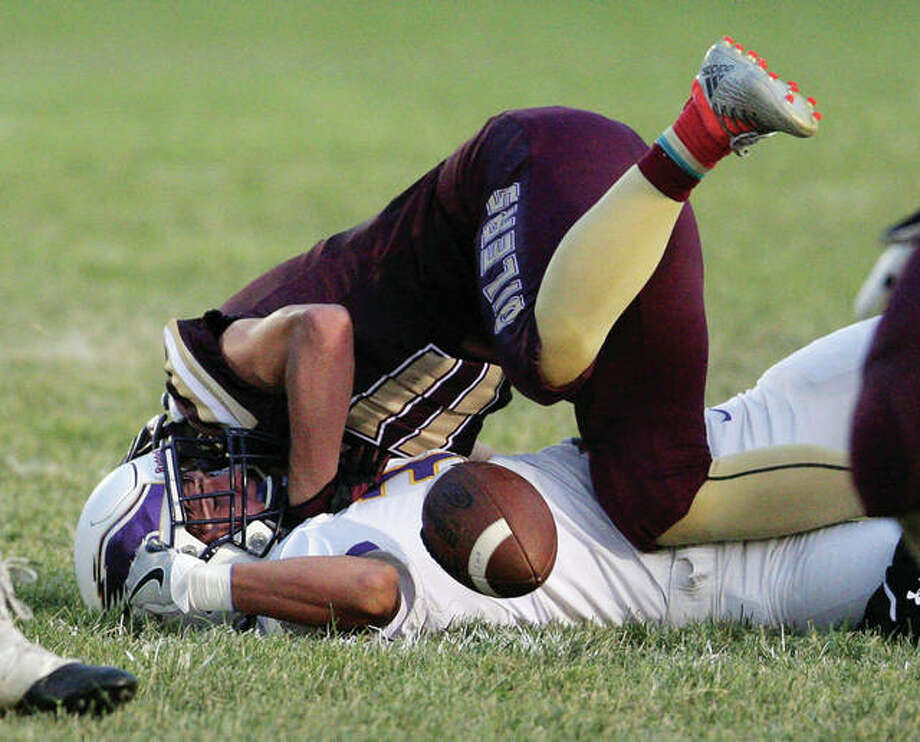 Civic Memorial's Noah Turbyfill (bottom) stops an East Alton-Wood River drive by hitting the Oilers' Brayden Young and forcing a fumble CM recovered during EA-WR's 21-7 Week 2 victory in Wood River. The 2-1 Oilers play at unbeaten Marquette on Friday night, while the Eagles open Mississippi Valley Conference play at unbeaten Triad. Photo: James B. Ritter / For The Telegraph
