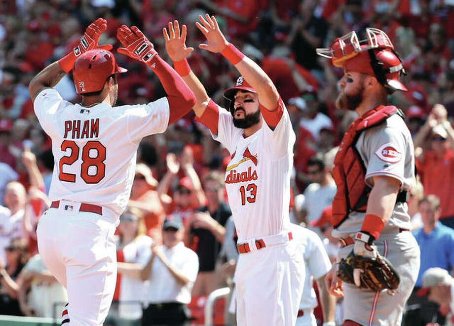 The Cardinals' Tommy Pham (28) is congratulated by Matt Carpenter after hitting a two-run home run as Reds catcher Tucker Barnhart stands by in the fifth inning Thursday at Busch Stadium. Photo: Associated Press