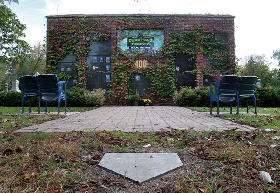 "Charles Rex Arbogast | AP A replica of Wrigley Field's outfield ivy walls, four stadium seats and a home plate called ""Beyond the Ivy"" is the final resting place for the ashes of nine Cubs fans at the Bohemian Cemetery. The Wrigley Field themed mausoleum wall was the dream of Dennis M. Mascari, who's ashes are just below the 400-feet marker."