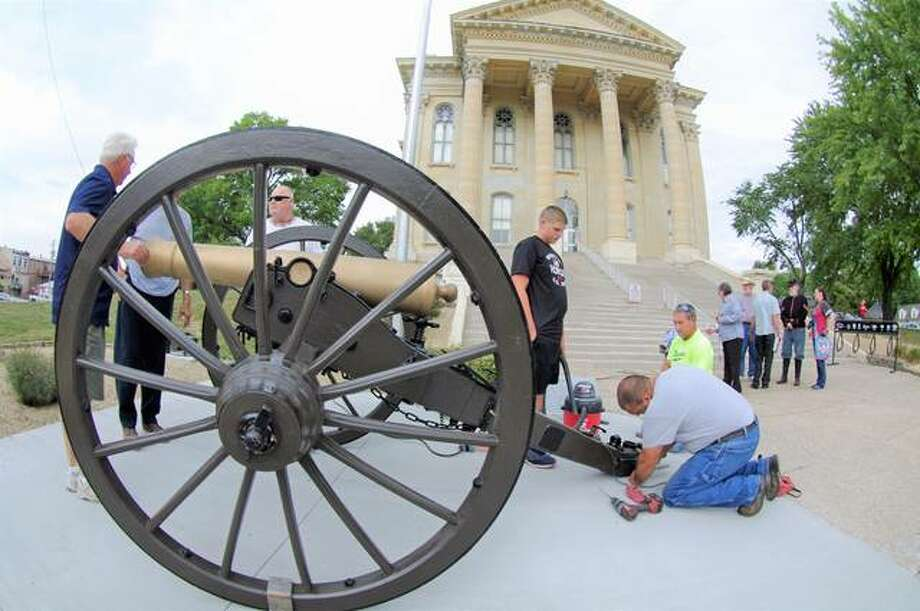 Workers from Koster Construction install brackets to hold a Civil War-era cannon in place in front of the Macoupin County Courthouse. The restored cannon was dedicated during a Sunday afternoon ceremony in Carlinville. Photo: Photos By David Blanchette | For The Telegraph