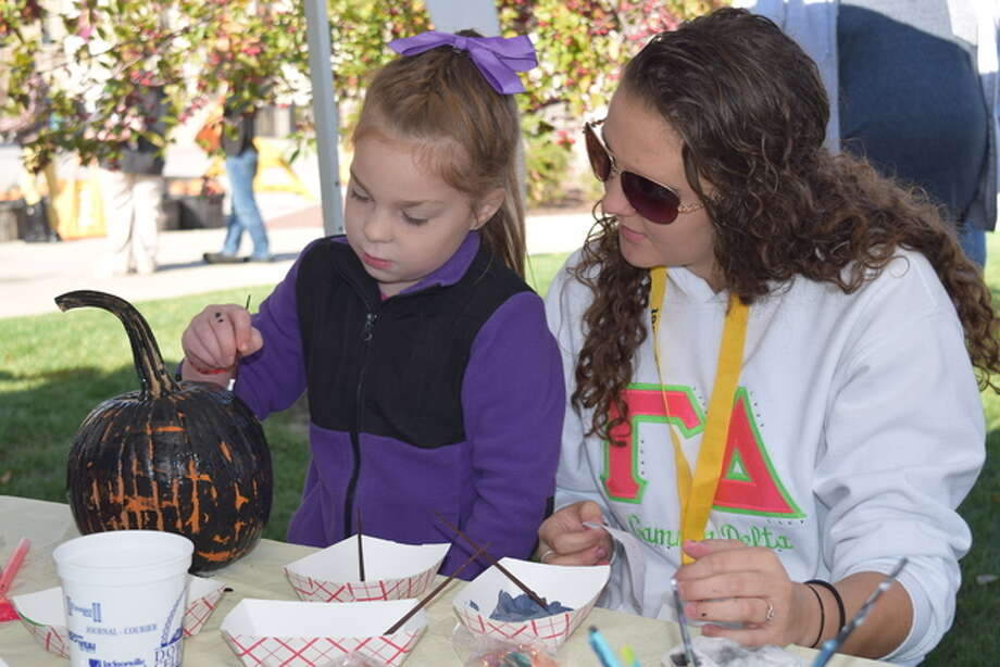 Saige McDade, 7, of Jacksonville decorates a pumpkin with Illinois College student and Gamma Delta Literary Society member Alyssa McElyea at the Jacksonville Main Street Pumpkin Festival on Saturday. Photo: Nick Draper | Journal-Courier