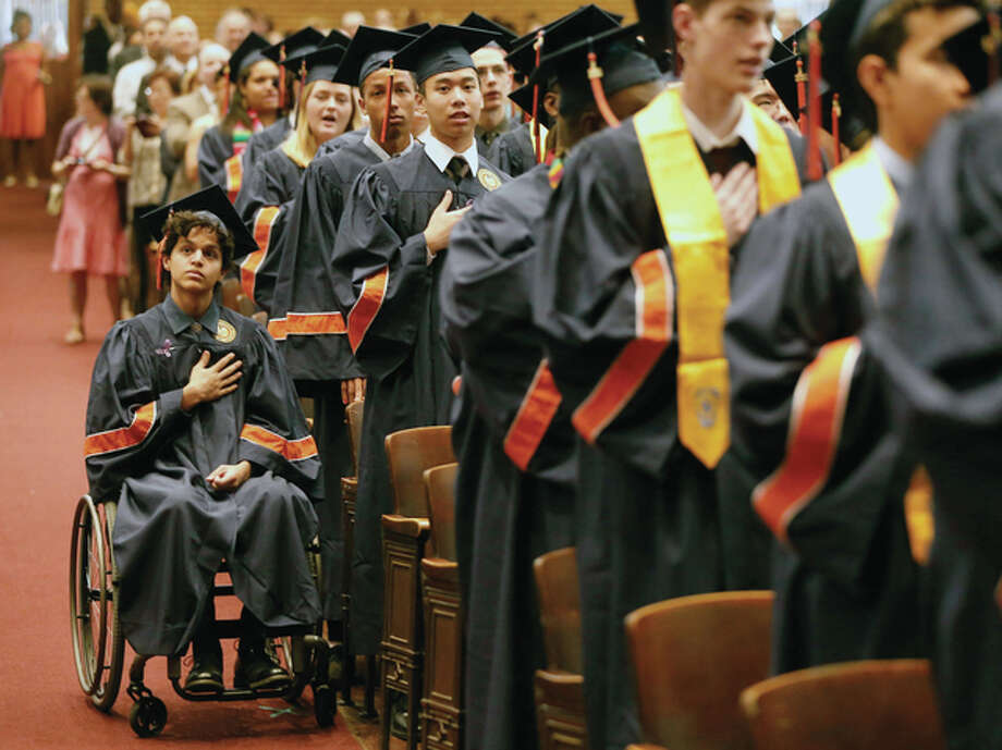 "Charles Rex Arbogast | AP Jonathan Annicks and fellow graduates listen to the national anthem during their high school graduation ceremony. His family's support and his desire keep him strong. ""If I crumble, then I feel like everything around me would, too. … I'm just living my life as I would normally and that's keeping everyone around me sane."""