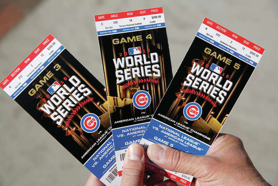 Michael Tercha | Chicago Tribune (AP) Chicago Cubs baseball fan Robert Lyons, who lives in Los Angeles and was raised in Berwyn, shows his World Series tickets outside Wrigley Field.