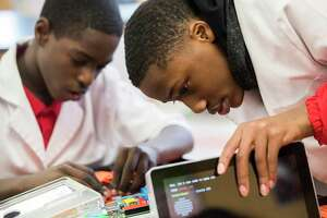 Bartley White, right, 14, and Lavaris Williams, left, 14, observe the hardware of a personal computer they were able to build with the assistance of Best Buy employees who volunteered to work with the eighth grade Fleming Middle School students, Friday, Feb. 9, 2018, in Houston.