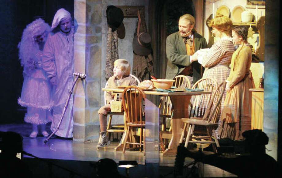 """The Ghost of Christmas Present, left, and Ebenezer Scrooge peer in on the Cratchit family during a production of Silver Dollar City's """"A Dickens Christmas Carol,"""" part of the 1880s-themed amusement park's """"An Old Time Christmas"""" festival. Photo: Scott Cousins
