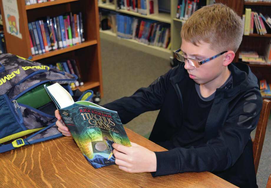 "Tyler Headen, the 12-year-old son of Katie and Jamie Headen of Jacksonville, reads ""The Hammer of Thor"" at the Jacksonville Public Library on Wednesday. The book is part of author Rick Riordan's series titled ""Magnus Chase and the Gods of Asgard."" Photo: Greg Olson 