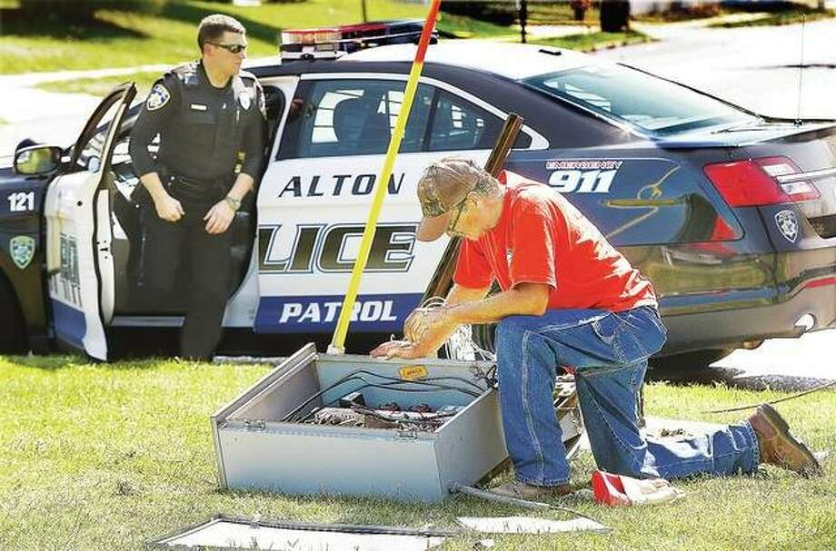 An employee of Wegman Electric disconnects and removes an electrical control box on Sept. 14 after a driver of a Chrysler 300 sedan jumped the curb at Statehouse Square in Alton, running over the equipment, which contained controls for the lighting and fountain. Photo: John Badman | The Telegraph