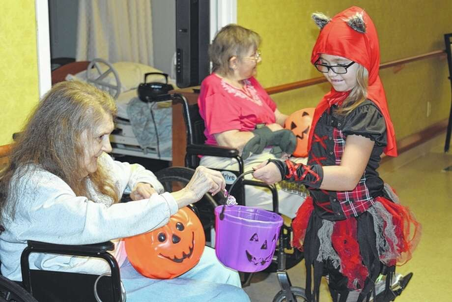 Autumn Hoots, 7, the daughter of Jeremy and Lisa Hoots, receives candy from Pat Boyer at the Aperion Care Trick-or-Treating event on Friday. Photo: Samantha McDaniel-Ogletree | Journal-Courier
