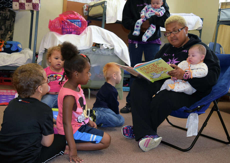 New Directions Warming & Cooling Center Executive Director Vanessa Tyus reads a book to some of the children staying at the shelter. Photo: Nick Draper | Journal-Courier
