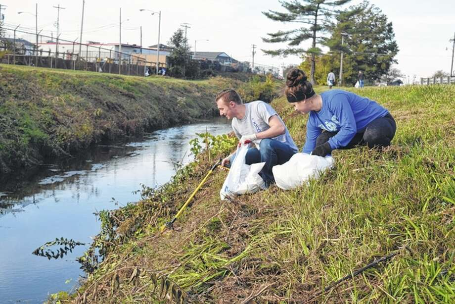 "Illinois College junior Sean Kisch of Elgin and IC senior Ellie Johnson of Virden pick up litter Saturday along Town Brook during the annual Town Brook Cleanup. Kisch and Johnson, who are members of IC's Alpha Phi Omega service fraternity, were among more than 75 volunteers who participated in the cleanup. The majority of the volunteers were IC students. ""The cleanup brings the community together,"" organizer Lori Oldenettel said. ""It helps to beautify the city while helping the environment."" Oldenettel said the city of Jacksonville received $500 from the Illinois Environmental Protection Agency this year to support the project. ""The community support and interest we've received over the past five years has been remarkable,"" she said. Photo: Greg Olson 
