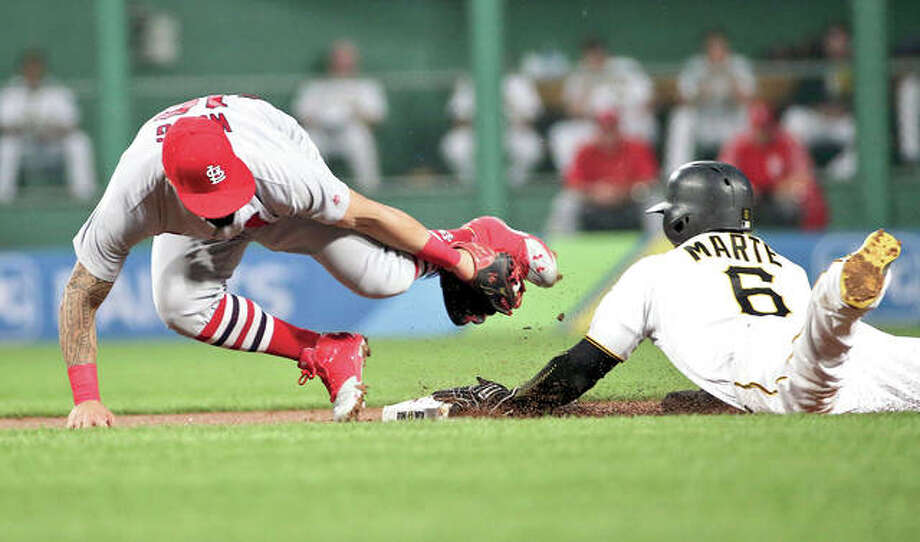 Cardinals second baseman Kolten Wong, left, tumbles as he tries to tag the Pirates' Starling Marte, who steals second base Friday night in Pittsburgh. Photo: AP