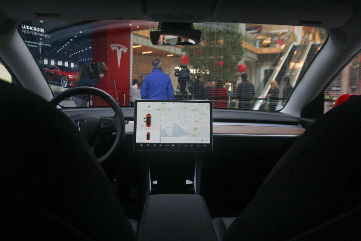 The interior of Tesla's newest car, the Model 3, is seen at the Bellevue Square Tesla showroom on Friday, Feb. 9, 2018. Deliveries to customers began in November, but with 450,000 reservations for the most affordable Tesla yet, many who hold reservations are still waiting for their cars.