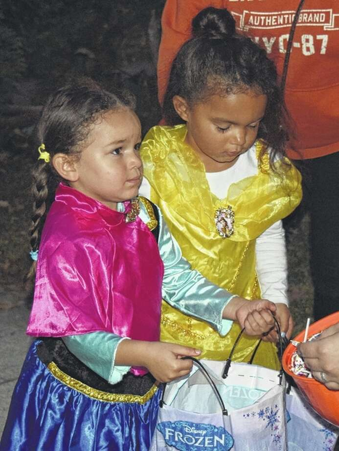 Averie Moore (left), 4, and Aliyah Harris, 3, go trick-or-treating Sunday night. Averie is the daughter of Jenna Moore of Jacksonville. Aliyah is the daughter of Rita and Johnny Harris of Jacksonville. Photo: Photos By Samantha McDaniel-Ogletree | Journal-Courier