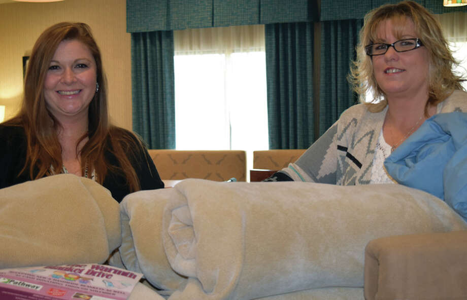 Brittany Henry (left) and Michelle Foreman-Smith are spearheading a blanket drive through the Jacksonville Area Convention & Visitors Bureau and Hampton Inn. Photo: Samantha McDaniel-Ogletree | Journal-Courier