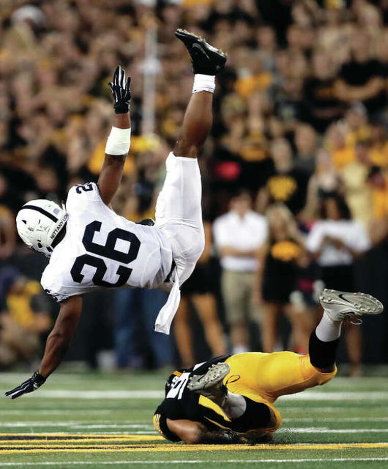 Iowa defensive end A.J. Epenesa, a freshman from Edwardsville, upends Penn State running back Saquon Barkley (26) during the first half Saturday night at Kinnick Stadium in Iowa City, Iowa. Penn State, ranked No. 4 in the country, scored on the game's final play to pull out a 21-19 victory over the Hawkeyes. Epenesa, The Telegraph Player of the Year with the Tigers in 2016, had a sack and forced fumble against Penn State. The 6-foot-5, 270-pound Epenesa leads the Hawkeyes in quarterback hits with four and second in sacks with 2.5. Photo: Associated Press