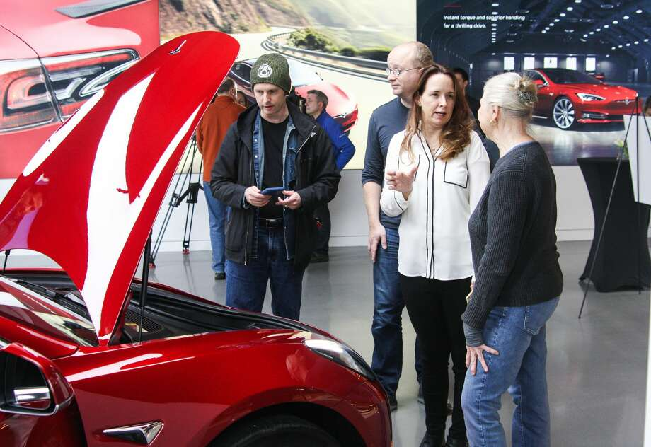 Margilee O'Neill talks with a Tesla representative about the company's new Model 3 at its Bellevue Square showroom on Friday, Feb. 9, 2018. Deliveries to customers began in November, but with 450,000 reservations for the most affordable Tesla yet, many who hold reservations are still waiting for their cars. Photo: DANIEL DEMAY / SEATTLEPI.COM