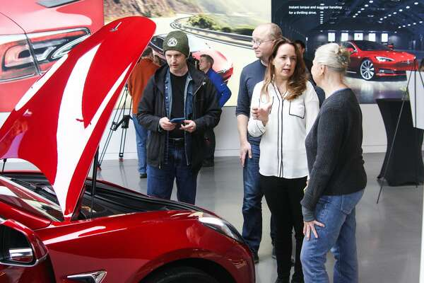 Margilee O'Neill talks with a Tesla representative about the company's new Model 3 at its Bellevue Square showroom on Friday, Feb. 9, 2018. Deliveries to customers began in November, but with 450,000 reservations for the most affordable Tesla yet, many who hold reservations are still waiting for their cars.
