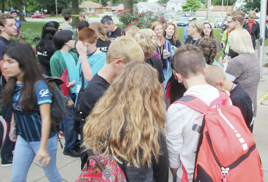 Students circles and prays as part of See You at the Pole last year at Roxana junior and senior high schools. About 100 students came out for the early-morning prayer time. This year's event is set for Wednesday at about 7:15 a.m.