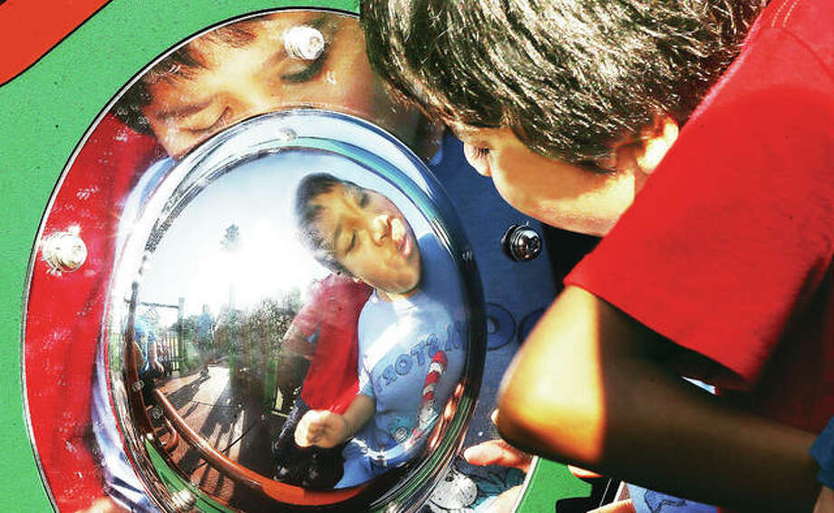 John Badman|The Telegraph An Alton School District student checks out his reflection in a reflective half circle Monday during the dedication ceremonies at Gordon Moore Park for the All Inclusive Playground which was finished over the weekend. The reflective circle was one of several visual attractions at the new playground.