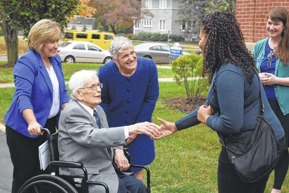 Pam Birdsell and Illinois College President Barbara Farley stand behind former Congressman Paul Findley as he shakes the hand of Illinois College archivist Porsha Butler outside of Whipple Hall on Thursday.