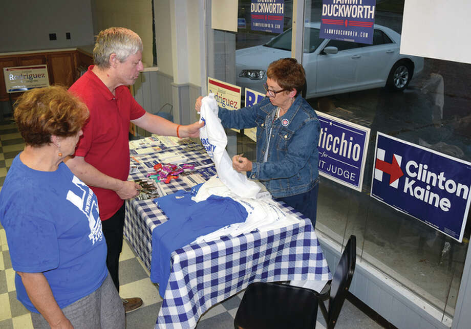 Judith Nelson (left), president of Morgan County Democrats, and Dana Ryan (right), chair of the Morgan County Democratic Central Committee, help Rob Stampf, a volunteer, select a shirt at Morgan County Democratic campaign headquarters on Mound Road. Photo: Greg Olson | Journal-Courier