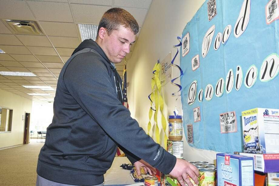Lincoln Land Community College sophomore Brock Reid of Bluffs stacks canned goods Monday as part of the college's food drive. Until Thanksgiving, the college will accept non-perishable food items that will be donated to the Jacksonville Area Community Food Center. The college also is a Toys for Tots drop-off center until Dec. 1 and, beginning at 10:30 a.m. Wednesday, is having a chili and hot dog sale to benefit Prairieland United Way. Photo: Nick Draper | Journal-Courier
