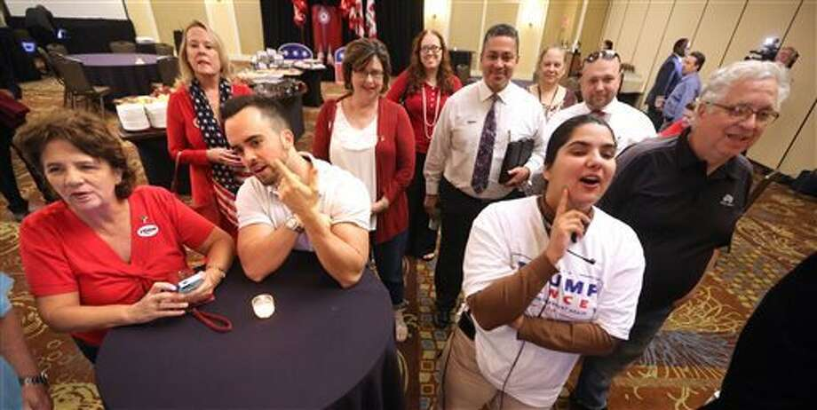 Republican voters watch election results, moments after first polls closed at 7 p.m. EST, during the Republican Party of Seminole County, Florida. Election Watch Party in Altamonte Springs, near Orlando, Florida, Tuesday. (Joe Burbank/Orlando Sentinel via AP)