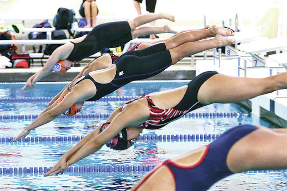 Swimmers hit the water off the starting blocks at a recent meet at Edwardsville High's Chuck Fruit Aquatic Center. Photo: Telegraph File Photo