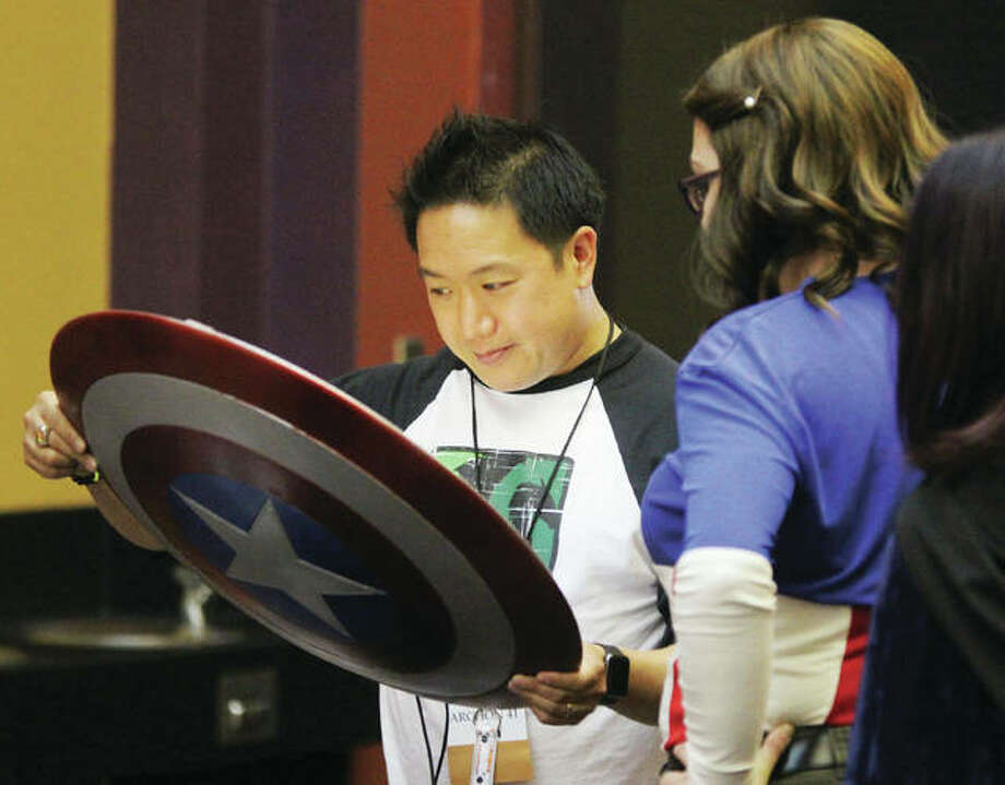 "Ming Chen, of the AMC television series ""Comic Book Men,"" looks at a ""Captain America"" shield that was part of a costume worn by Kayla Deevers, of Festus, Missouri, at ARCHON, a science fiction/fantasy convention held annually in Collinsville. This years convention, which continues through Sunday, is expected to draw approximately 2,300 people. Photo: Scott Cousins 
