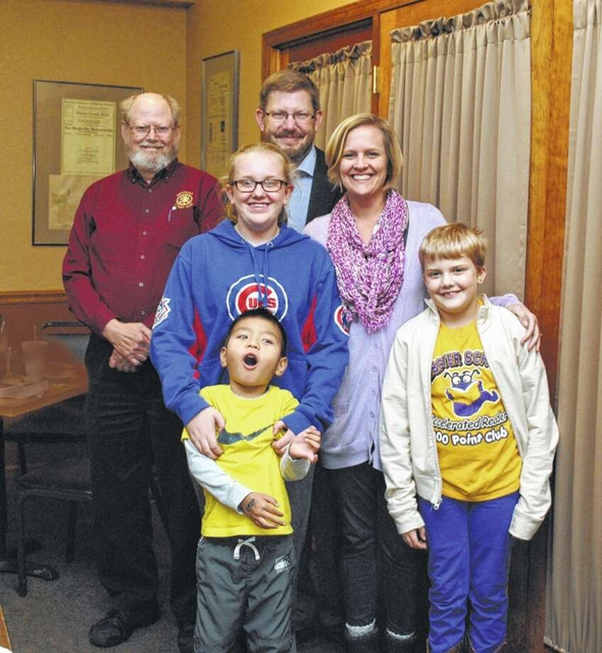Rushville Rotarian Ron Robeson (top left) stands with the Grant and Amy Armstrong family after the family presented on their recent adoption from China. Grant Armstrong (back right), his wife, Amy (middle right), and daughters Lilli (middle left), 11, and Clara (front right), 8, gained a new addition to their family this summer when they adopted Theo (front right), 4, from China. Photo: Photo Submitted