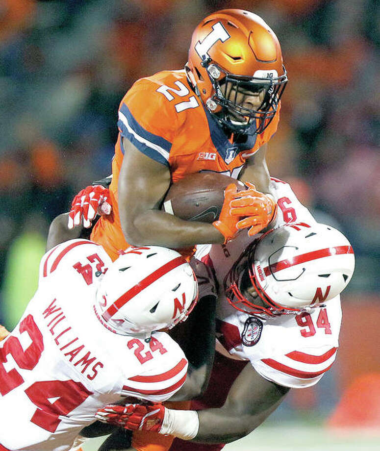 Illinois running back Ra'Von Bonner (21) carries as Nebraska defensive back Aaron Williams (24) and defensive lineman Khalil Davis (94) converge on him Friday night in Champaign. Photo: AP