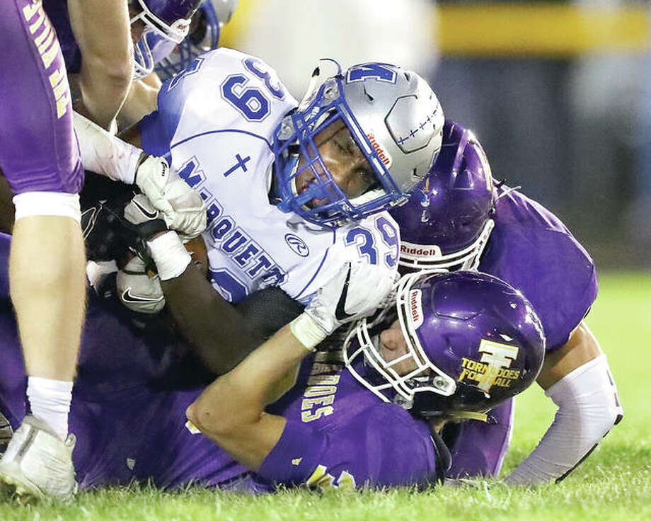 Marquette's Aaron Gregory (39) is tackled by a host of Taylorville defenders during Friday night's game at Taylorville High School. Photo: Billy Hurst | For The Telegraph